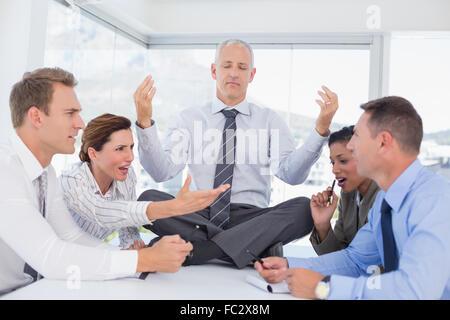 Imprenditore rilassante sulla scrivania con sconvolto i colleghi circa Foto Stock