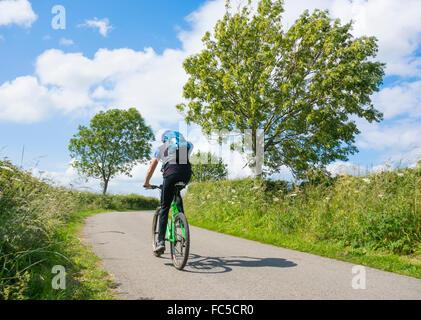 Mountain Biker su una tranquilla strada di campagna dello Yorkshire Dales National Park, nello Yorkshire, Inghilterra, Foto Stock