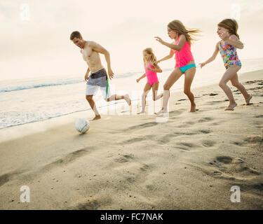Padre caucasica e le figlie che giocano a calcio sulla spiaggia Foto Stock