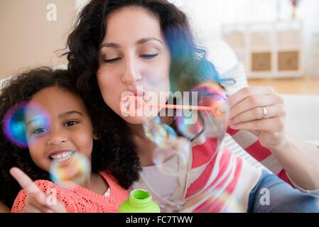 Madre e figlia a soffiare bolle Foto Stock