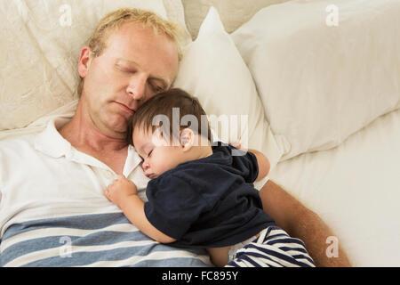 Padre e Figlio bambino che dorme sul letto Foto Stock
