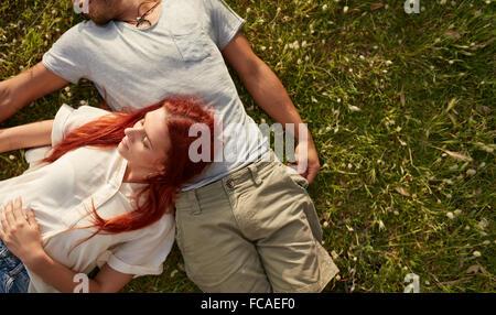 Giovane donna sdraiata sul prato con il suo fidanzato. Vista aerea della coppia giovane rilassante sull'erba, con copia spazio. Foto Stock