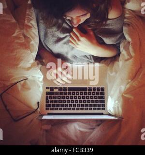 Direttamente sopra il colpo di giovane donna utilizzando laptop sul letto Foto Stock