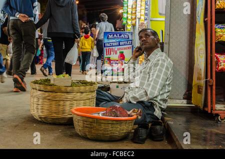 Povero indiano venditore stradale perso in pensieri, pensando, seduto sulla strada principale, città bazaar, mahabaleshwar, Foto Stock
