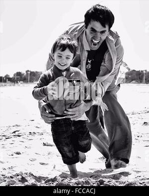 Padre giocando a rugby gioco con il figlio sulla spiaggia Foto Stock