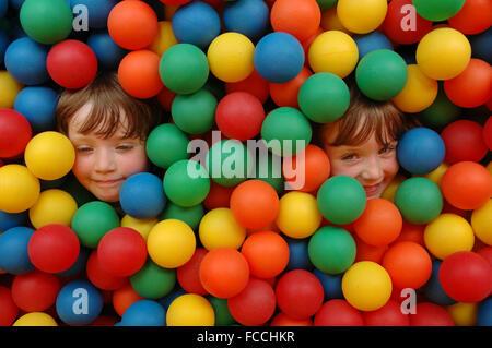 Carino sorella e fratello circondato da coloratissime palle