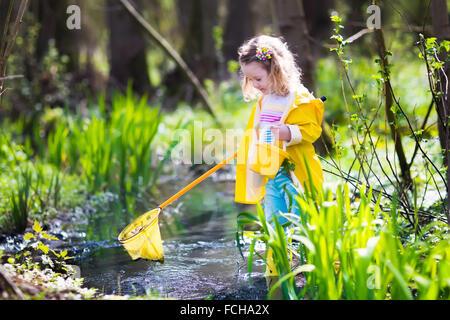 Bambini che giocano all'esterno. I bambini di età prescolare la cattura di rana con net. Un ragazzo e una ragazza Foto Stock
