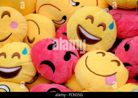 Viso arrabbiato in una folla di volti sorridenti Foto Stock