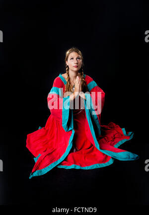 Studio shot di una giovane e bella ragazza in abbigliamento medievale in ginocchio a pregare (su sfondo nero) Foto Stock