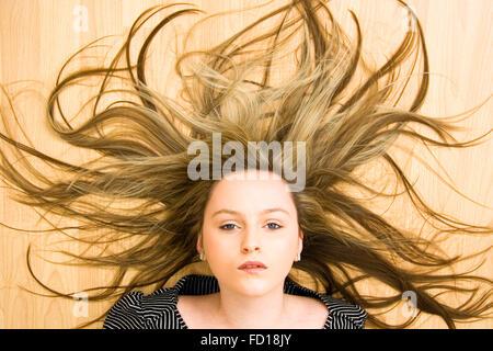 Testa e spalle, adolescente bionda dagli occhi blu ragazza posa sul pavimento cercando direttamente al visualizzatore. Foto Stock