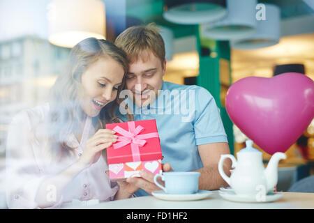 Giovane donna sorpresa aprendo il suo fidanzato regalo in cafe Foto Stock