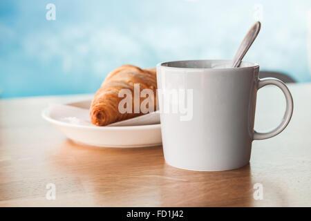 Cappuccino con croissant. Tazza di caffè con schiuma di latte si erge su un tavolo di legno nella caffetteria blu Foto Stock