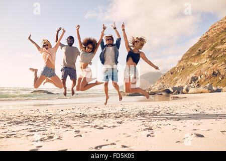 Gruppo di amici sulla spiaggia di divertimento. Felice giovani salto sulla spiaggia. Gruppo di amici gustando estate vac Foto Stock