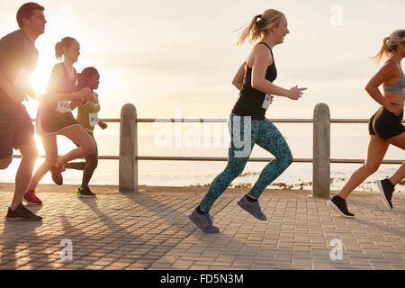 Ritratto di giovani in esecuzione sul lungomare. Gli uomini e le donne della maratona in esecuzione su strada sul mare al tramonto. Foto Stock
