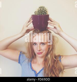 Ritratto di giovane donna sorridente che porta Vaso di fiori sulla testa contro la parete a casa Foto Stock