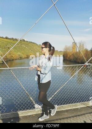 Per tutta la lunghezza della donna in piedi sul passaggio pedonale su fiume contro Sky Foto Stock
