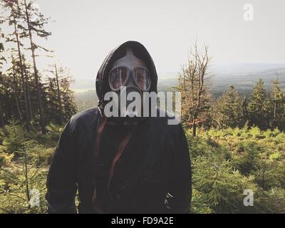 Vista frontale di uomo che indossa maschera a gas nella foresta contro il cielo chiaro Foto Stock