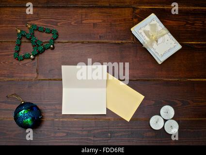 Sfera ad albero di natale con carte sul tavolo di legno Foto Stock