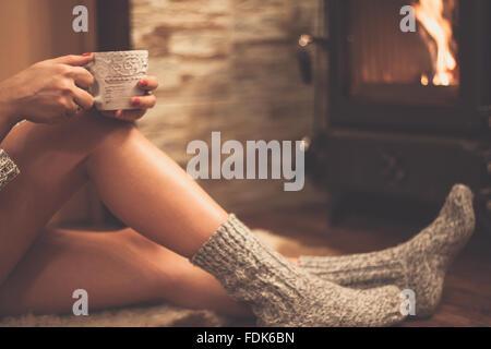 Donna seduta davanti a una stufa a legna con la tazza di tè Foto Stock