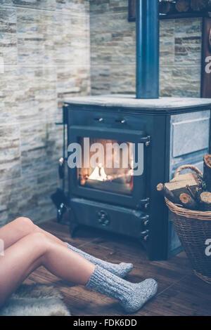 Donna seduta davanti a una stufa a legna Foto Stock