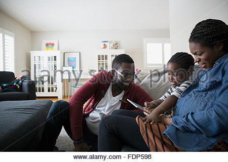 La famiglia tramite tavoletta digitale sul divano Foto Stock