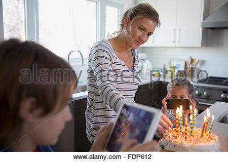 Madre e bambini fotografare la torta di compleanno con candele Foto Stock