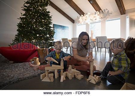 Madre e figli giocare i blocchi di legno albero di Natale Foto Stock