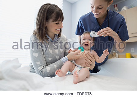 L'infermiera utilizzando termometro su Gridando bambino sala esame Foto Stock
