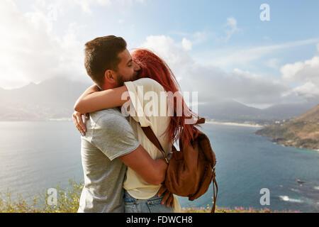 Ritratto di una felice coppia giovane godendo di un romantico abbraccio all'esterno. Giovane uomo abbracciando la sua ragazza mentre in piedi su una collina