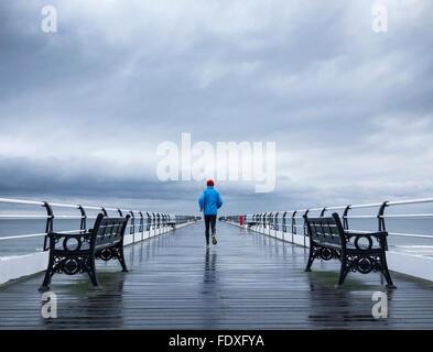 Uomo maturo di jogging sul Saltburn pier sotto la pioggia. Saltburn dal mare. North Yorkshire. Regno Unito Foto Stock