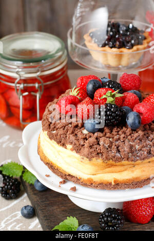 Cheesecake al cioccolato topping decorati con frutta estiva: lamponi, fragole, mirtilli e more. Foto Stock