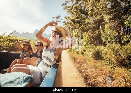 Ritratto di un allegro giovane donna seduta nella parte posteriore del carrello di prelievo con gli amici. Giovani Foto Stock
