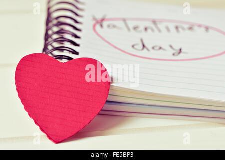 Primo piano di un cuore rosso e un notebook con il testo il giorno di San Valentino in manoscritti, su di una superficie Foto Stock
