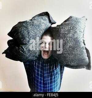 Ritratto di uomo urlando mentre trasportano i cuscini contro uno sfondo bianco