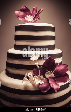 Dettagli di un matrimonio o una torta di compleanno, Dimensioni triple, in studio su sfondo bianco. Viola di fiori Foto Stock