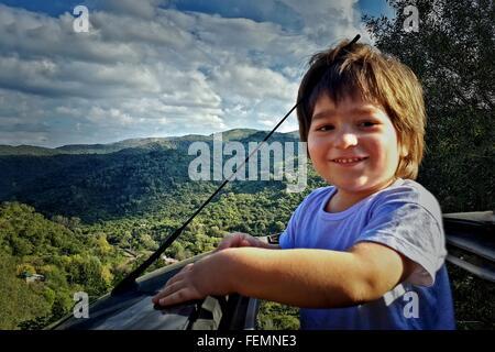 Felice ragazzo in piedi fuori auto del tettuccio apribile Foto Stock
