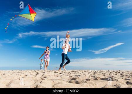 Famiglia di quattro battenti un aquilone sulla spiaggia. Foto Stock