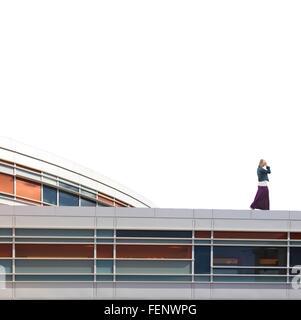 Vista laterale della Donna che cammina sulla sommità dell'edificio Foto Stock