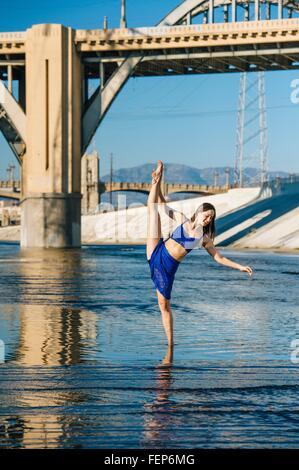 Ballerino profondo della caviglia in acqua, gamba sollevata, in equilibrio su una gamba, nella parte anteriore del Foto Stock