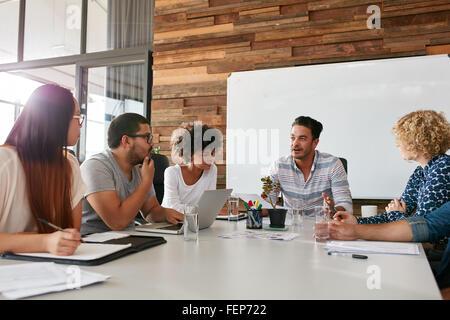 Inquadratura di un gruppo di giovani professionisti di aziende aventi una riunione nella sala riunioni. Gli impiegati Foto Stock