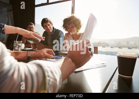 Le mani del giovane uomo e donna spiegando business plan ai colleghi, team creativo avente una riunione in ufficio. Foto Stock