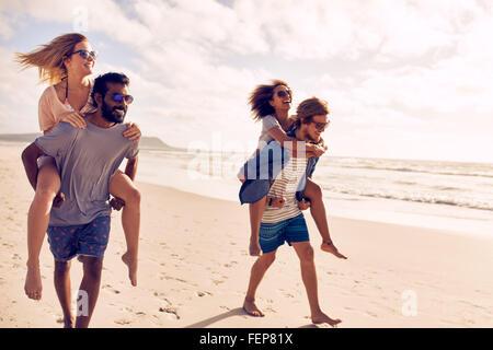 Due belle coppie giovani a piedi dalla spiaggia, con gli uomini che trasportano le loro donne sul loro retro. Le Foto Stock