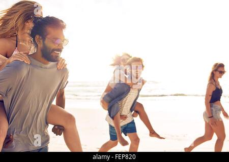 Gruppo di amici divertendosi sulla spiaggia, giovani uomini piggybacking donne sulla riva del mare. Razza mista Foto Stock