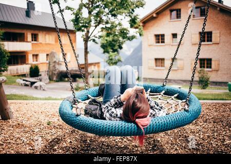 Ragazza adolescente giacente su swing amaca nel parco giochi utilizzando lo smartphone, Bludenz, Vorarlberg, Austria Foto Stock