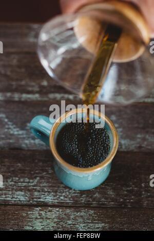L'uomo versando il caffè dal filtro caffettiera Foto Stock