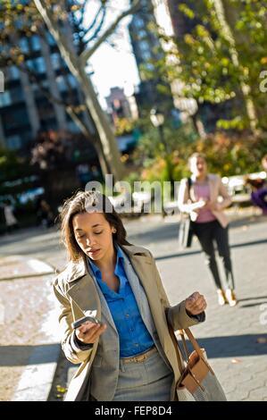 Giovane donna lettura mentre lo smartphone a piedi attraverso il parco della città