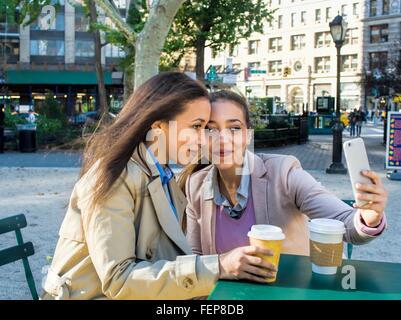 Giovane femmina adulta gemelli tenendo selfie nel parco della città Foto Stock