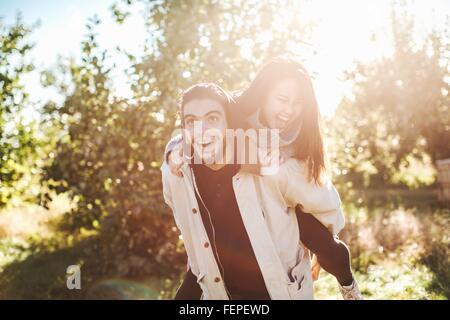Giovane uomo dando giovane donna piggyback ride, all'aperto Foto Stock