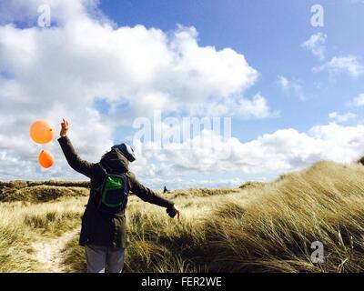 Vista posteriore della ragazza con palloncini di colore arancione sul campo contro il cielo nuvoloso Foto Stock