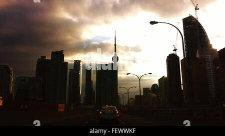 Silhouette in città con la CN Tower contro il cielo nuvoloso al tramonto